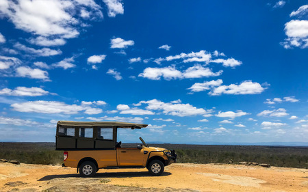 Pickup car tourist cat stop at viewpoint with beautiful blue sky and cloud in Kruger National Park, South Africa.