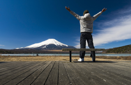 Traveller stand on lake side with cold wheather and looking to Fuji mountain