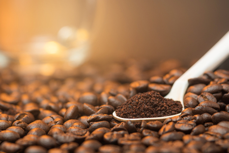 Close up cofee powder in the white spoon over coffee beans