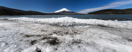 Beautiful Fuji mountain at cold lakeside with ice over the water and blue sky