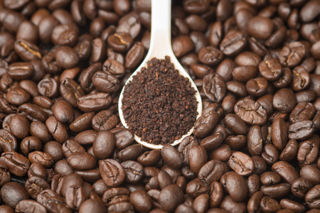 Topview Coffee powder in the white Spoon over the coffe beans