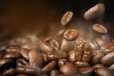 Coffee beans dropping in to pile of coffee beans roasting with smoke Stockfoto