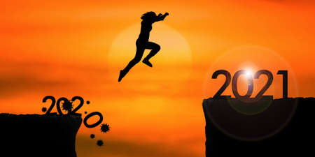 Silhouette woman jumping from 2020 cliff to 2021 cliff on sunrise time Standard-Bild
