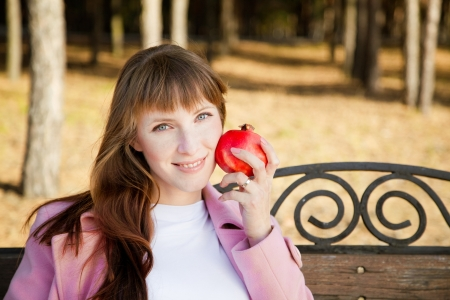 Beautiful young woman with fruit in park