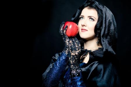 Woman in schwarzen Umhang mit Kapuze holding red apple
