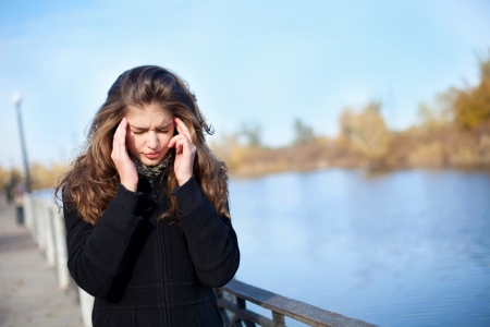Young woman with headache in park  Stock Photo