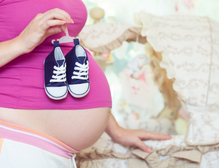 Pregnant woman holding  baby clothing Stock Photo