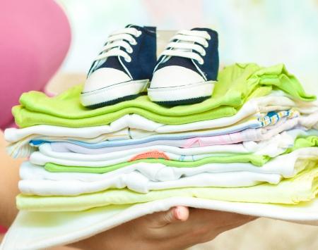 Schwangere Frau mit Stapel von Babykleidung