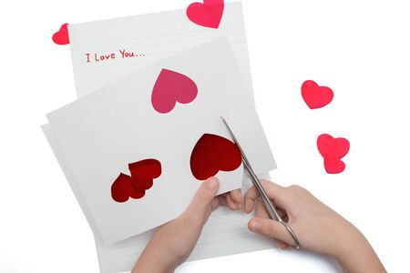 cut red hearts out of paper with scissors Фото со стока