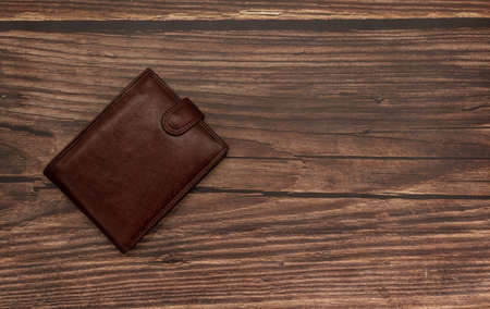 Closed brown wallet on wooden brown background 免版税图像 - 157880913