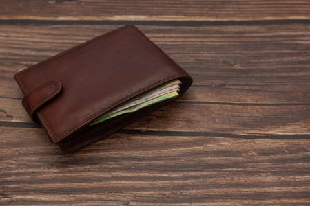 Closed mens brown wallet on a wooden brown background with money. Close-up