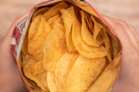 Hands hold a bag of potato chips. Junk food made from cholesterol. Salty and crispy. Fast food snack. Yellow color.