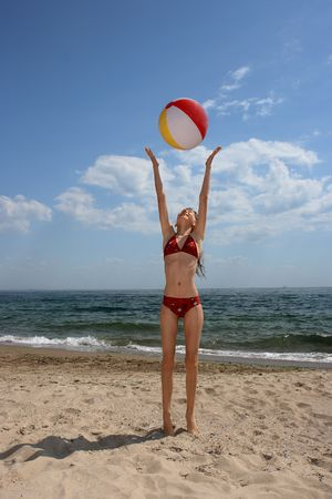 The girl plays a inflatable ball on the beach photo