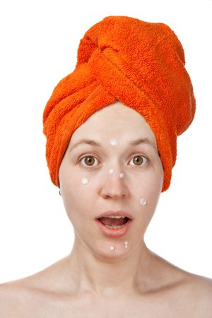 consternation: The girl with an open mouth, anti-akne cream on the face and orange towel Stock Photo