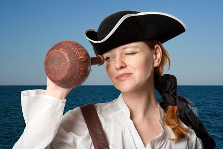 cocked: The girl-pirate in a cocked hat against the sea looks in a jug