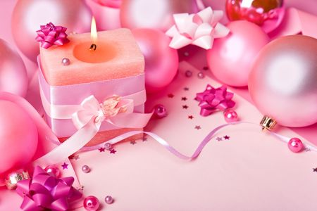 Burning candle and New Years spheres in pink tones photo