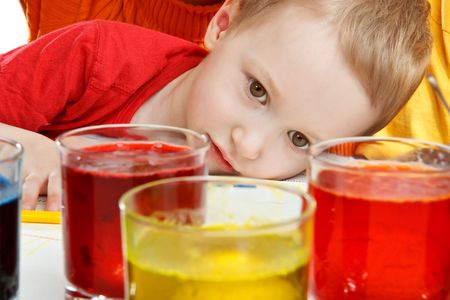 observes: The little boy observes of process of colouring of egg in a glass Stock Photo