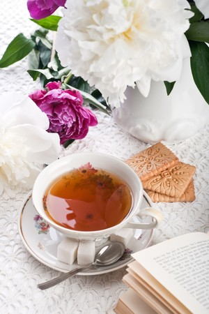 Tea with cookies, the book and flowers on lacy cloth photo
