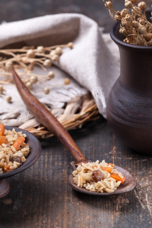 Wooden spoon with rice pilaf on the kitchen table photo