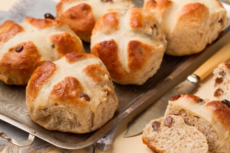 Freshly baked cross buns on a metal tray  horizontal shot  Stock Photo