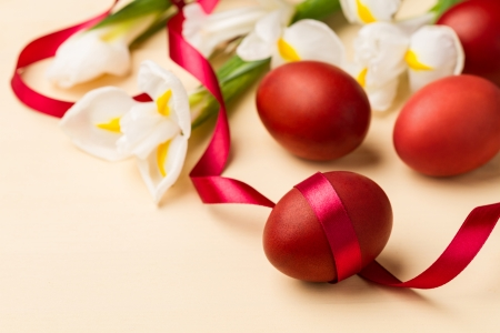 Easter eggs, white flowers and red ribbon on the beige table