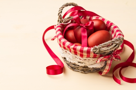 Easter eggs in a basket with red checkered napkin on beige table