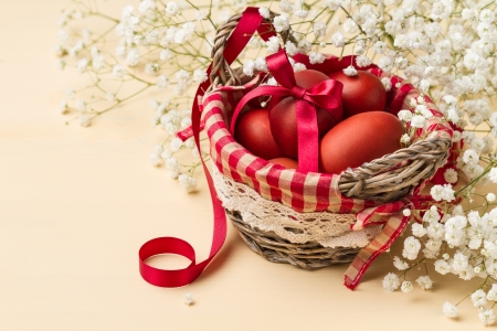 Easter eggs in a basket with red checkered napkin and white flowers horizontal shot