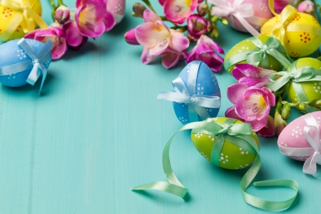 Colored Easter eggs with ribbons and flowers on a turquoise table  horizontal shot  photo