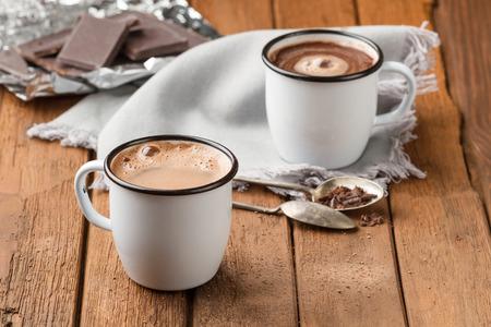 두 개의 에나멜 머그컵에 거품이있는 핫 초콜릿