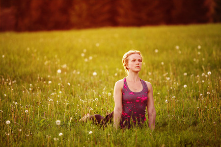 Young woman in a relaxing yoga pose at the evening meadow Stock Photo