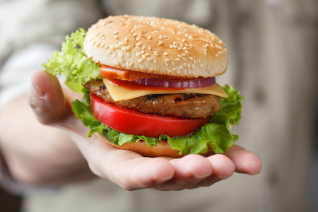 eating fast food: Fresh tasty burger in the mans hand Stock Photo