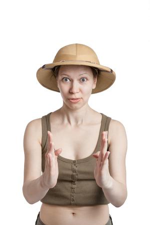 médula: La muchacha divertida en un casco tropical mantiene las palmas delante de sí mismo en un backgroung blanco Foto de archivo