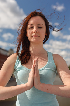flying hair: Young woman with flying hair in meditation pose Stock Photo
