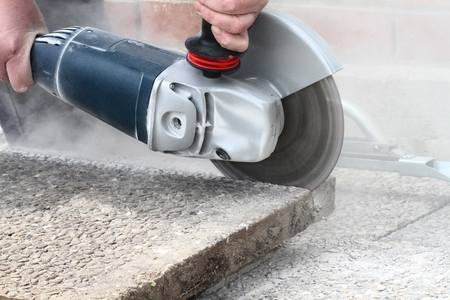 Industrial construction worker using a professional angle grinder. photo