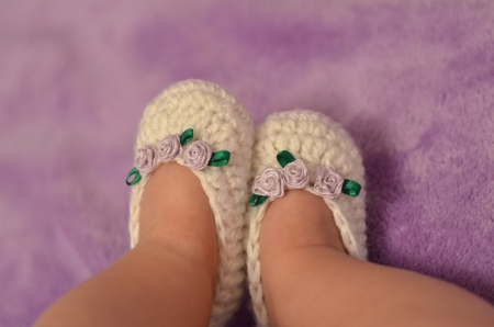 sneaks: baby legs in knitting white slippers with purple roses on the arm Stock Photo