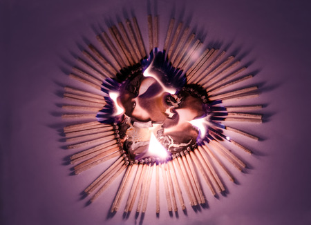 Heart shape from matches in Fire on Purple background photo
