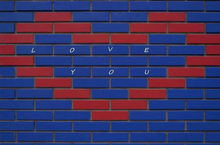 rectangulo: Nueva Te Amo pared de ladrillos de múltiples colores en la casa en la calle Foto de archivo