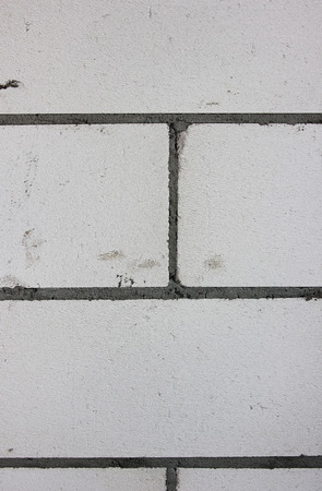 The building wall background. Grey bricks of the cement basis. Detail of the wall and texture of the Construction