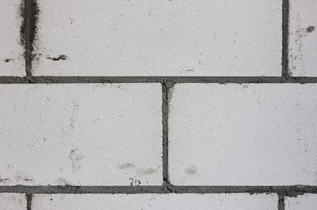 The building wall background. Grey bricks, cement. Detail