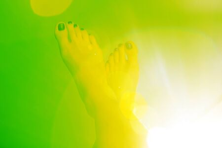 a pair of the foot on a green color background with yellow halo-effect. The creative concept for leaflet or other ideas