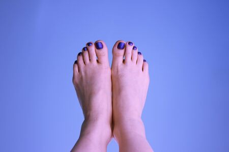The beauty woman`s feet with a pedicure on a blue background. The summer mood