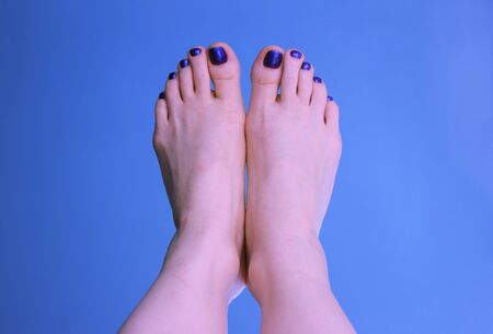 The pair of a woman`s feet with a blue pedicure on a blue background. The summer mood