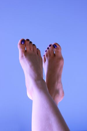 The woman feet with a blue pedicure on a blue background. The summer mood Banco de Imagens