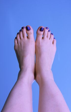 The woman`s feet with pedicure on a blue background. The summer mood