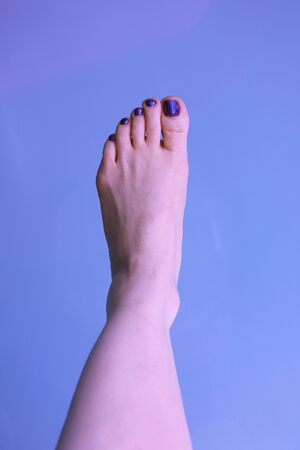 The woman`s left foot on a blue background. The summer mood
