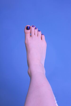 The woman`s right foot wiht a pedicure on a blue background. The summer mood