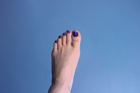 The woman`s left foot with a pedicure on a blue background. The summer mood Banco de Imagens