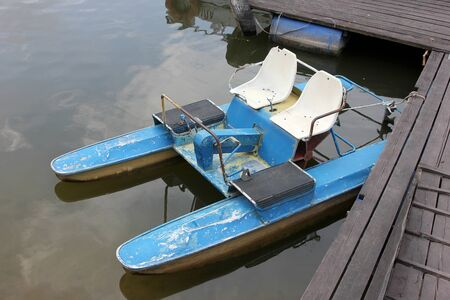 The old blue catamaran on the banks of the river. The summer resting outdoor
