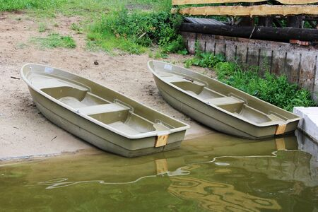 Two plastic boats on the banks of the river Istra. Summer, fishing, vacation on the river Banco de Imagens