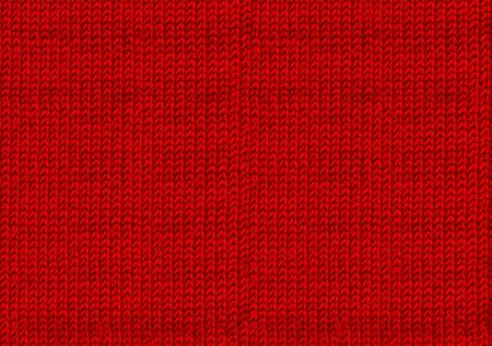 Red knitted woolen christmas background. The atmosphere of a warm sweater. New year backdrop. Texture of the wool or acrylic knit. Base for winter design
